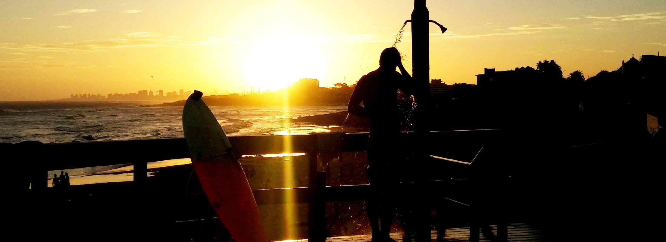 ducha en la playa con la puesta de sol